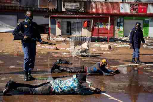 South African police make suspected looters lie down and roll in muddy water.